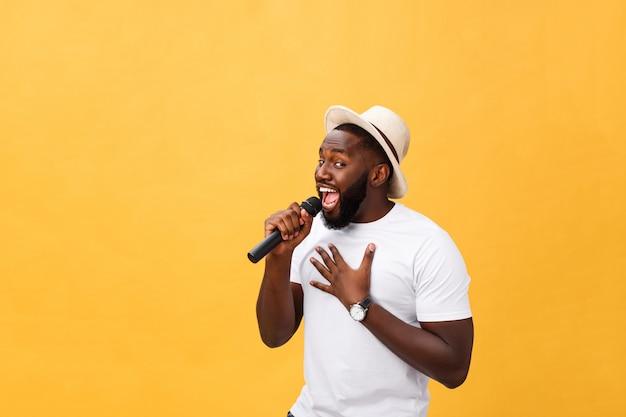 Jeune beau garçon afro-américain chantant émotionnel avec microphone isolé sur fond jaune Photo Premium