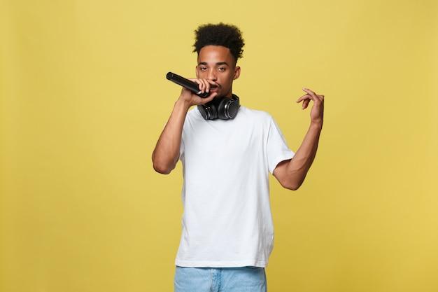 Jeune beau garçon afro-américain chanter l'opéra émotionnel avec microphone. Photo Premium