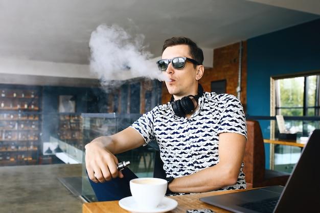 Jeune beau hipster homme insunglasse assis dans le café avec une tasse de café, vaping et libère un nuage de vapeur Photo Premium