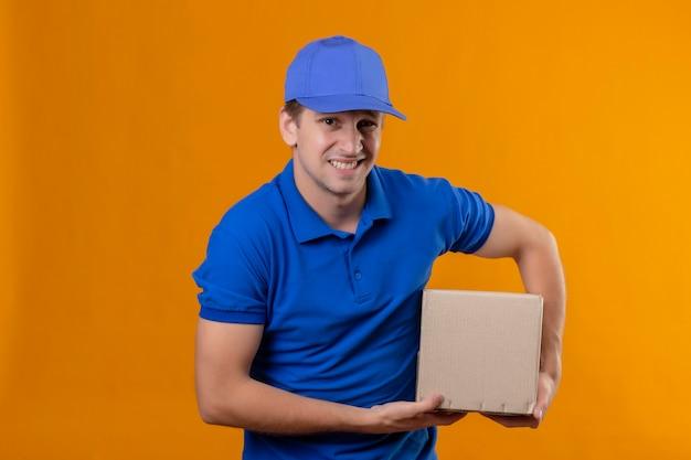Jeune Beau Livreur En Uniforme Bleu Et Cap Holding Box Package Mécontent D'une Expression Dégoûtée Photo gratuit