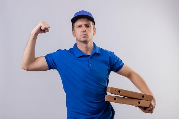 Jeune Beau Livreur En Uniforme Bleu Et Cap Tenant Des Boîtes à Pizza Levant Le Poing Montrant Les Biceps Photo gratuit