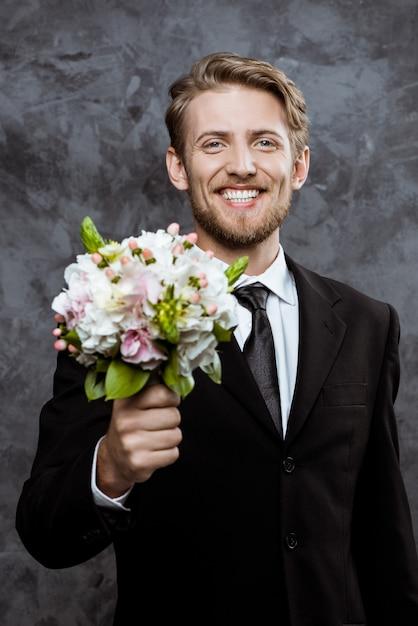 Jeune Beau Marié Souriant, Tenant Un Bouquet De Mariée Photo gratuit