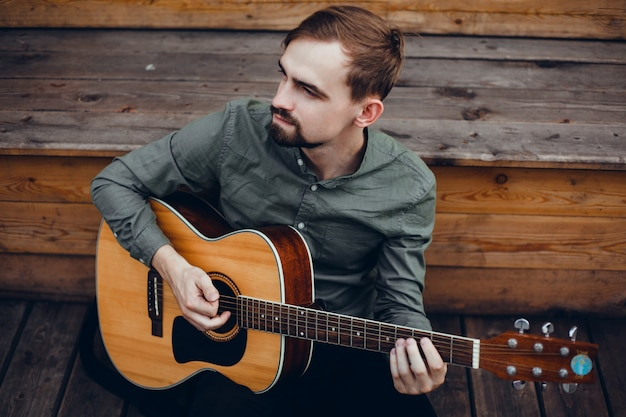 Jeune beau mec joue de la guitare, ramasse un accord, musicien de rue Photo gratuit