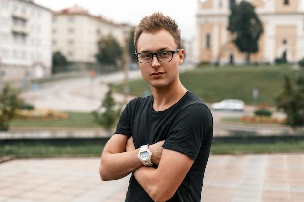 Jeune Beau Mec à Lunettes Noires Et Un T-shirt Noir Photo Premium