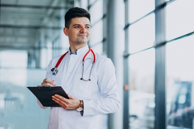 Jeune beau médecin dans un peignoir médical avec stéthoscope Photo gratuit