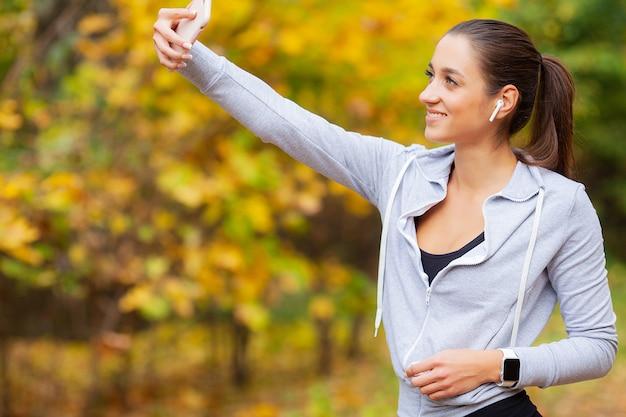 Jeune beauté aux longs cheveux bruns regardant un smartphone prenant une photo d'elle-même Photo Premium