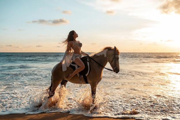 Jeune beauté brune s'amuser avec cheval et équitation plage tropicale Photo Premium