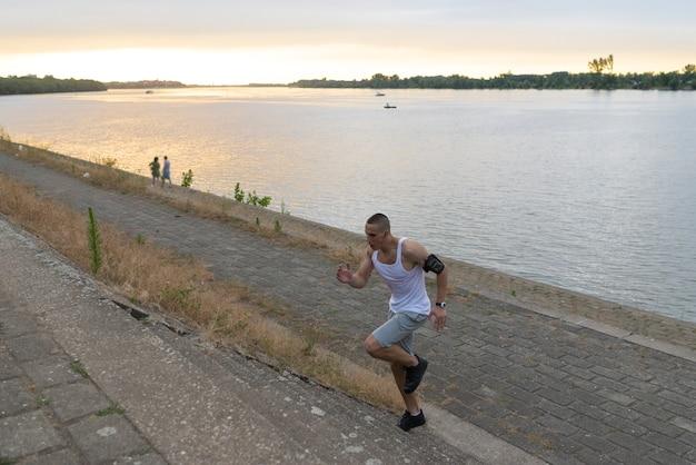 Jeune bel athlète courant en haut de la rivière Photo Premium