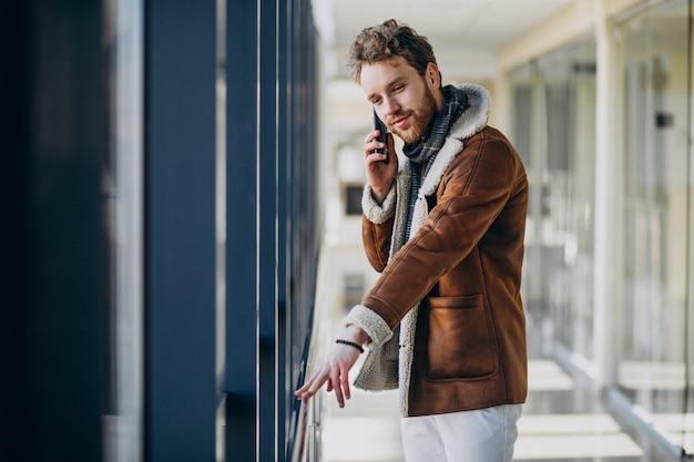 Jeune Bel Homme à L'aéroport, Parler Au Téléphone Photo gratuit