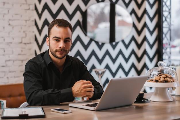Jeune bel homme d'affaires travaillant sur ordinateur portable au café moderne. Photo Premium