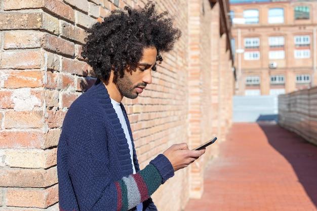 Jeune bel homme africain à l'aide de son smartphone avec sourire tout en s'appuyant sur un mur de briques Photo Premium