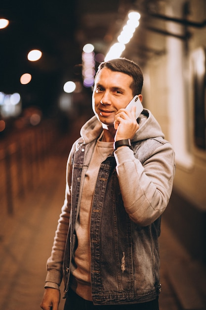 Jeune bel homme à l'aide de téléphone la nuit dans la rue Photo gratuit