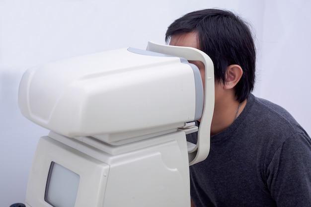 Jeune Bel Homme Asiatique Prendre Un Examen De La Vue Avec Une Machine De Test Oculaire Optique Photo Premium