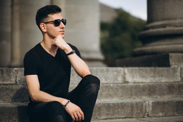 Jeune bel homme assis dans les escaliers Photo gratuit