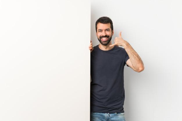 Jeune bel homme à la barbe faisant un geste de téléphone Photo Premium