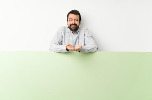 Jeune bel homme à la barbe avec une grande pancarte vide Photo Premium