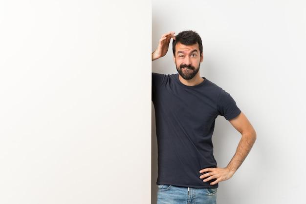 Jeune bel homme à la barbe tenant une grande pancarte vide ayant des doutes tout en grattant la tête Photo Premium