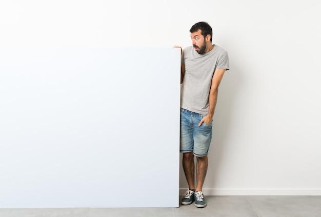 Jeune bel homme à la barbe tenant une grande pancarte vide bleue avec une expression faciale surprise Photo Premium