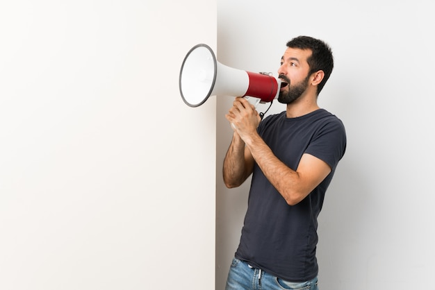 Jeune bel homme à la barbe tenant une grande pancarte vide criant à travers un mégaphone Photo Premium