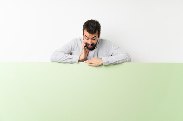 Jeune bel homme à la barbe tenant une grande pancarte vide verte Photo Premium