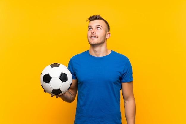 Jeune bel homme blond tenant un ballon de football sur un mur jaune isolé, levant en souriant Photo Premium