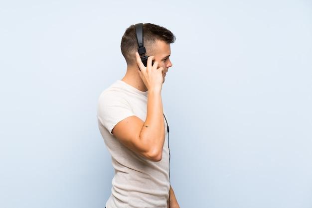 Jeune bel homme blonde sur un mur bleu isolé, écouter de la musique avec des écouteurs Photo Premium