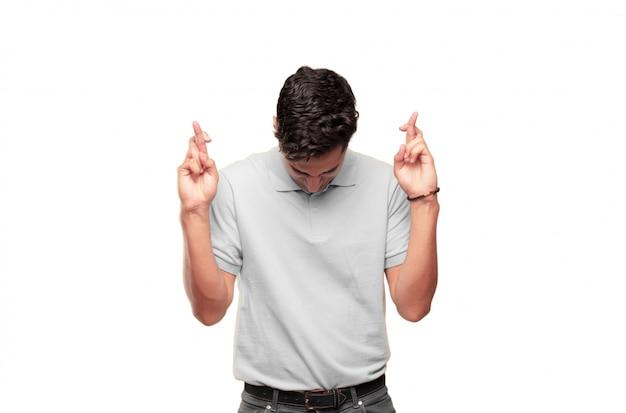 Jeune bel homme bronzé souriant malencontreusement en jurant une promesse, tricher, croiser les doigts Photo Premium