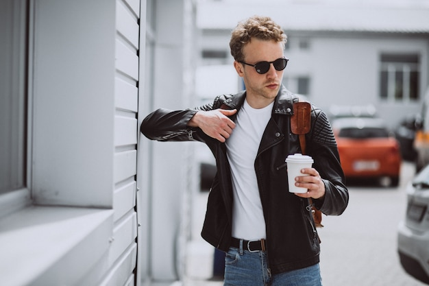 Jeune bel homme buvant du café dans la rue Photo gratuit