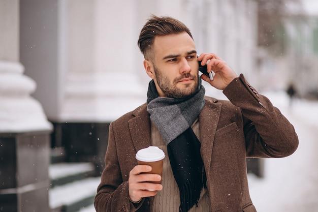Jeune bel homme buvant du café et parler au téléphone Photo gratuit