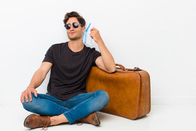 Jeune Bel Homme Avec Une Carte D'embarquement, Billets Assis Sur Le Sol Dans Une Salle Blanche Photo Premium