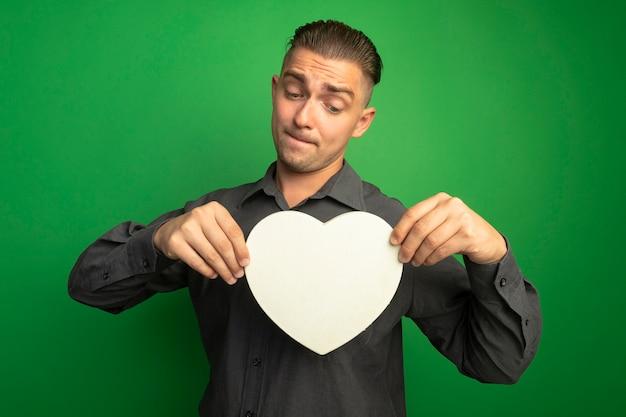 Jeune Bel Homme En Chemise Grise Montrant Coeur En Carton En Le Regardant Avec Une Expression Confuse Debout Sur Un Mur Vert Photo gratuit