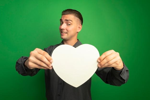 Jeune Bel Homme En Chemise Grise Montrant Coeur En Carton En Le Regardant Avec Une Expression Confuse Photo gratuit
