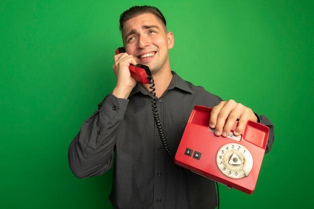 Jeune Bel Homme En Chemise Grise Parlant Au Téléphone Vintage Souriant Joyeusement Debout Sur Le Mur Vert Photo gratuit