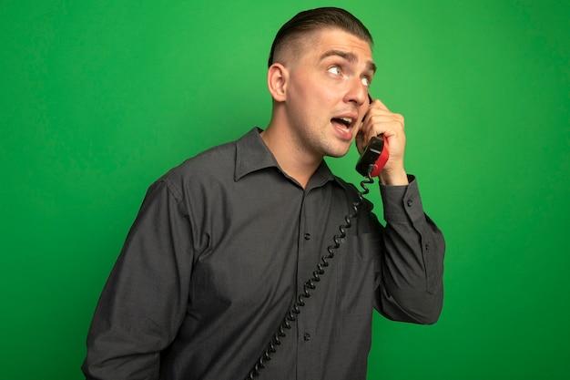 Jeune Bel Homme En Chemise Grise Parler Sur Téléphone Vintage à Côté Confus Debout Sur Mur Vert Photo gratuit