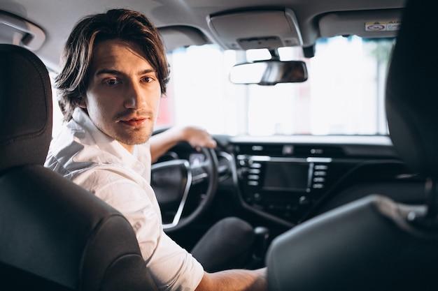 Jeune bel homme choisissant une voiture dans une salle d'exposition Photo gratuit