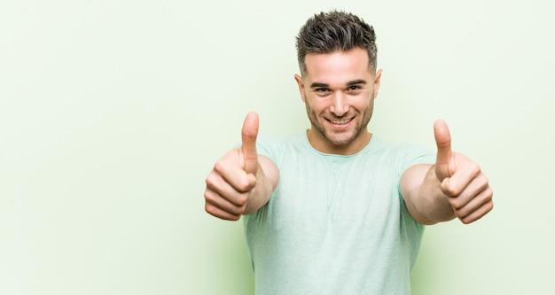 Jeune bel homme contre-vert avec pouce levé, acclamations, soutien et respect. Photo Premium