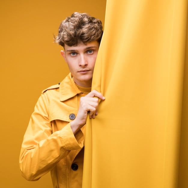 Jeune bel homme à côté d'un rideau dans une scène jaune Photo gratuit