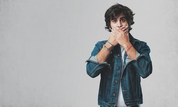 Jeune bel homme couvrant la bouche, symbole du silence et de la répression, essayant de ne rien dire Photo Premium