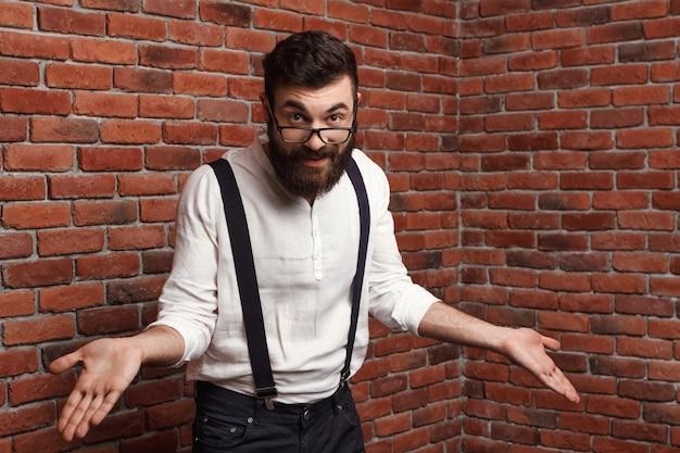 Jeune Bel Homme Dans Des Verres, Gesticulant Sur Le Mur De Briques. Photo gratuit