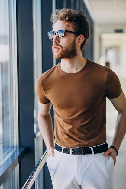 Jeune Bel Homme Debout Près De La Fenêtre à L'aéroport Photo gratuit