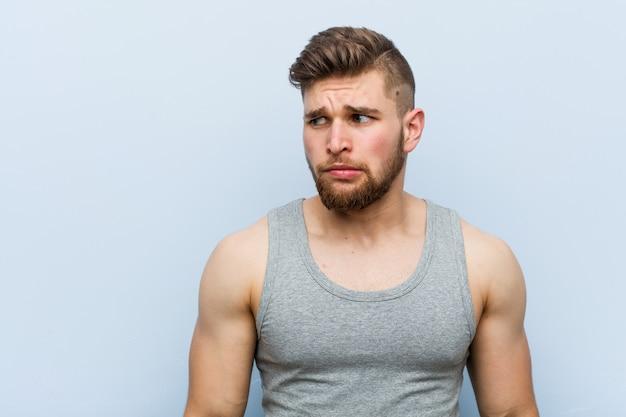Jeune bel homme de fitness confus, se sent douteux et incertain. Photo Premium