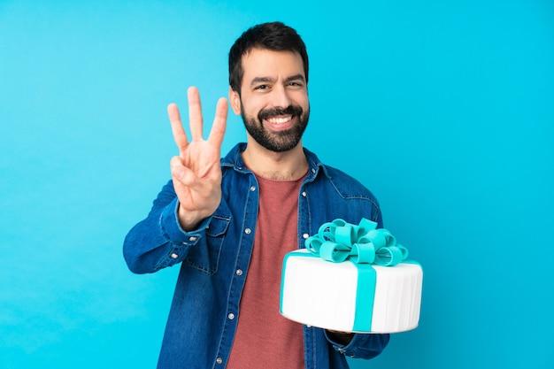 Jeune Bel Homme Avec Un Gros Gâteau Sur Le Mur Bleu Isolé Heureux Et En Comptant Trois Avec Les Doigts Photo Premium