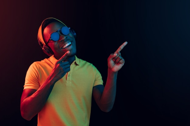 Le Jeune Bel Homme Hipster Heureux écoute De La Musique Avec Des écouteurs Au Noir Avec Des Néons Photo gratuit