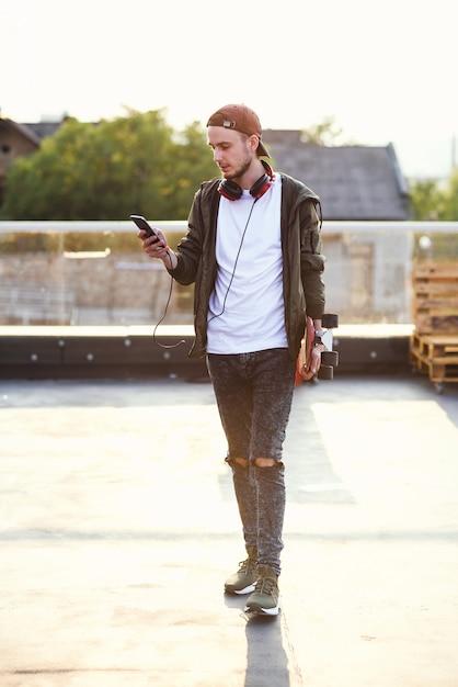 Jeune Bel Homme Hipster Avec Planche à Roulettes à L'aide De Téléphone Sur L'aire De Jeux Sur Le Toit Du Bâtiment Industriel. Photo Premium