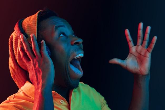 Le Jeune Bel Homme Hipster Surpris Heureux écoute De La Musique Avec Des écouteurs Au Noir Avec Des Néons Photo gratuit