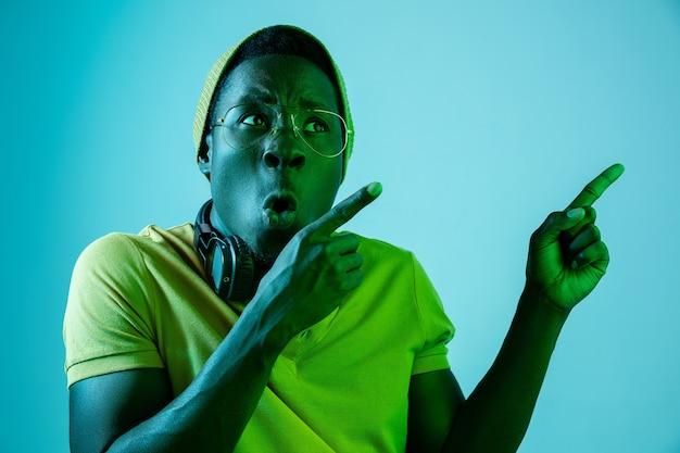 Le Jeune Bel Homme Hipster Surpris Heureux écoute De La Musique Avec Des écouteurs Avec Des Néons Photo gratuit