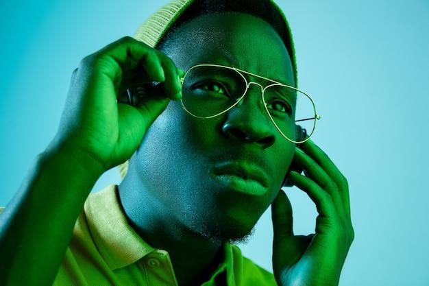 Le Jeune Bel Homme Hipster Triste Grave écoute De La Musique Avec Des écouteurs Avec Des Néons Photo gratuit