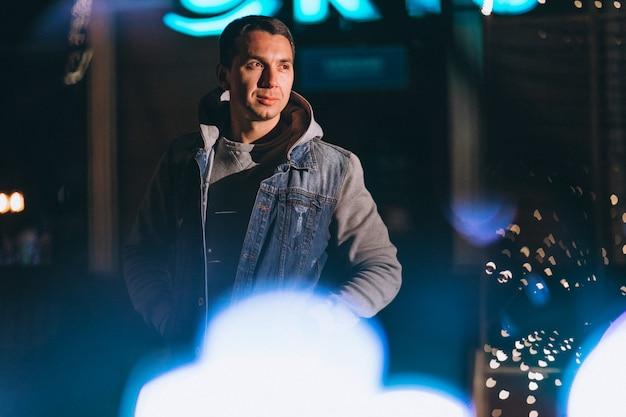 Jeune bel homme marchant le soir en dehors de la rue Photo gratuit