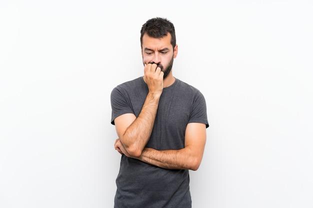Jeune Bel Homme Sur Mur Blanc Isolé Ayant Des Doutes Photo Premium