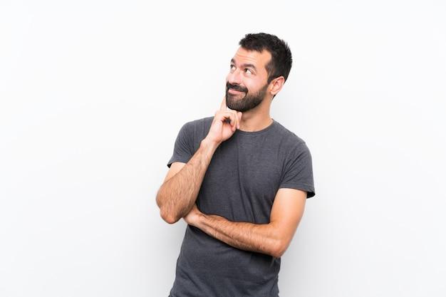 Jeune Bel Homme Sur Mur Blanc Isolé, Pensant Une Idée Tout En Levant Photo Premium